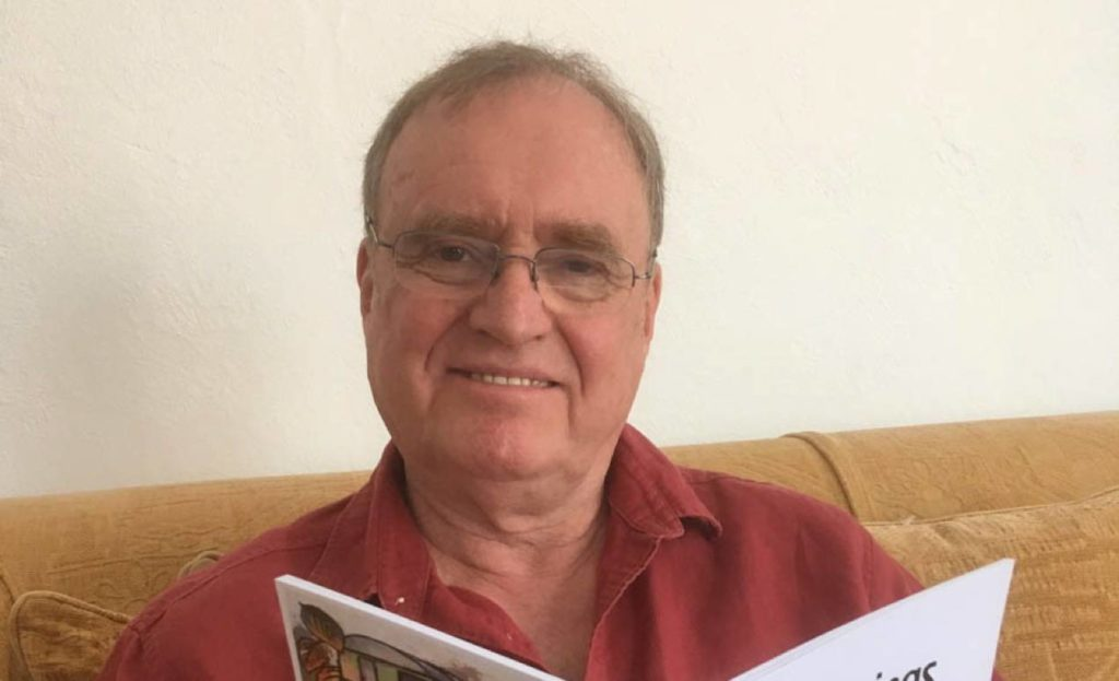 Trevor Hughes with his poetry collection which charts his relationship with his son Peter